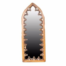 Gothic Carved Wood Wall Mirror: A carved oak wall mirror. This mirror is housed in a wood frame carved in the shape of a gothic window frame, with an arched overall shape and partial florets as embellishment. Outer edges are artfully imperfectly angled.