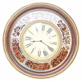 Round Wall Clock: A round wall clock. This round wall clock is presented in a round wood frame that has gold tone and wood tone with a painted mirror that has scrolling detail that matches the wood tone.
