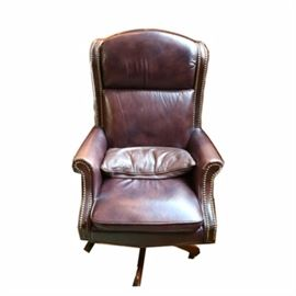 Executive Style Leather Office Chair: An executive style leather office chair. The chair features brass nailhead trim and brown leather upholstery to its padded backrest, armrests, and cushioned seat. It stands on four wooden legs atop four swivel metal casters.