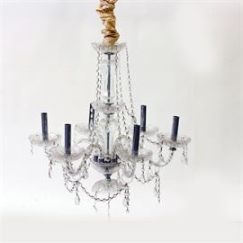Traditional Glass Chandelier: A traditional style glass chandelier. The light has a glass bowl crown with glass bead garland and a silver-tone center pole that is surrounded by turned glass.The chandelier has a chrome metal base with holders that displays six curved metal and twist style glass arms. Other features of the light include glass bowl pans with a diamond pattern and scalloped edges holding chrome metal sleeve sockets, a glass bowl cap and pear-shaped prisms and glass garland throughout. This item coordinates with item # 17LAX304-042 and 17LAX304-043.