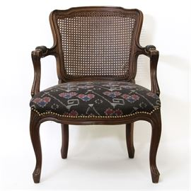 Vintage Louis XV Style Fauteuil: A vintage Louis XV style fauteuil. This chair features a curved crest rail and wicker back panel with padded armrests rising on curved arm supports flanking an upholstered seat. The chair features brass nailhead trim over thin apron sides rising on cabriole legs terminating on pad feet. The seat is upholstered in a black fabric with blue, grey, and red details. There are no visible maker's marks.