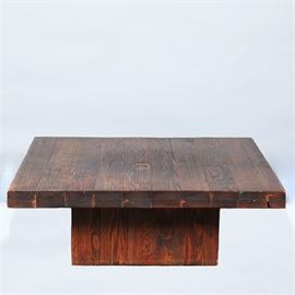 Oak Coffee Table: An oak coffee table. This square top table constructed of oak planks with dark stain sits on a raised square base. There are no visible maker's marks.