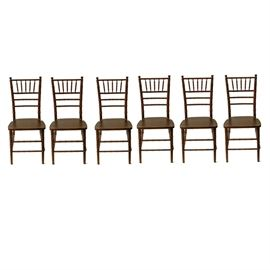 Six Chiavari Style Chairs: A collection of six Chiavari style chairs. Each chair features a spindle crest with spindle support rails and stiles, all including ring turnings. The chair each include a panel seat with cut-out curves at the hips and rise up on turned legs with stretchers of the same ring turned design. The chairs include mahogany veneers.