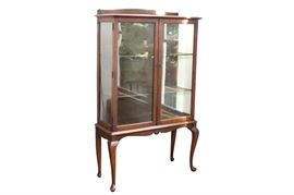 "Antique Queen Anne Mahogany China Cabinet: A Queen Anne mahogany china cabinet having two glass front locking doors opening to three illuminated shelves with plate grooves. It is raised on 20"" high Queen Anne legs with pad feet. This piece is located on the main level of the home."