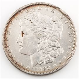 1892 Silver Morgan Dollar: An 1892 silver Morgan dollar. Designer: George T. Morgan. Mintage: 1,036,000. Metal content: 90% silver, 10% copper. Diameter: 38.1 mm. Weight: approximately 26.7 grams. It appears that this coin has been cleaned. The coin is circulated and in fair condition.