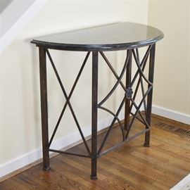 Granite Top Iron Demilune Entry Table: A granite top demilune iron entry table. The removable black granite top covers a bronze patina iron demilune shaped table base. The table features a lattice design with a center floral medallion and square iron legs. Unmarked.