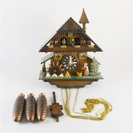 Reuge Fröhliche Wanderer Cuckoo Clock: A Reuge Fröhliche Wanderer cuckoo clock by Romance. This Swiss made clock is a chalet design, no. 3888. It depicts a woman with a bucket, a mill, and flower decorated window boxes. It includes three pinecone weights and a wood pendulum.