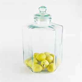 Glass Beverage Dispenser: A hexagonal beverage dispenser. In a tinted green glass, this flat bottom dispenser includes a brass valve and glass lid. Twelve faux lemons are included.