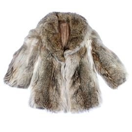 Vintage Coyote Fur Coat: A vintage coyote fur coat. The hip-length fur coat is in shades of cream and brown, featuring long sleeves and a shawl collar. It is fully lined with a personalized signature, and is not labeled.