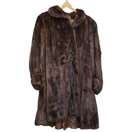 "Vintage Mink Fur Coat: A vintage mink fur coat. The long coat has a rounded collar, long sleeves with cuffs, and hook fasteners up the front. It is lined in brown satin, and labeled ""Made in Hong Kong""."