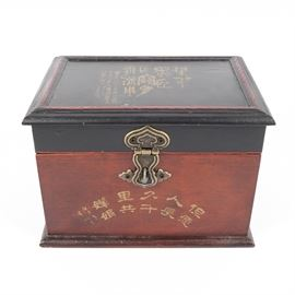 Chinese Hand-Painted Wooden Box: A Chinese wooden lidded box. This vintage piece features hand-painted gold tone Chinese characters to the black lid and reddish-brown wood. The box has a decorative brass tone latch to the front and brass tone hinges to the back.