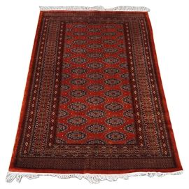 "Red Persian Rug: A handwoven Persian area rug. The rug features a center panel with staggered guls on a rust background, in a palette of black, orange, white and rust. The center panel is framed by multiple patterned borders with resolved corners. The two ends have wide borders with a small diamond pattern, and are finished with white fringe. No maker's marks. The back side of the rug has a handwritten number along one edge ""H 43141""."