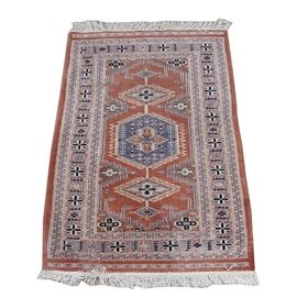 Handwoven Turkish Rug: A handwoven Turkish area rug. The rug features Dyrnak guls on a rust colored background, in a palette of blue, light gray, taupe, cream and black. The center panel is framed by a floral border featuring cross-like flowers alternating with climbing vine motifs, and the corners are unresolved. The two short ends have borders similar to the guard borders, and are finished with white fringe. No maker's marks.
