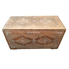Mother of Pearl Inlay Chest: A vintage carved and inlaid wooden trunk with mother-of-pearl. The rectangular trunk or chest has a a hinged lid, which currently lifts off, and features relief carved leaf designs and geometric star motifs with white mother-of-pearl inlay throughout. The interior is stained a light pink color. No maker's marks.