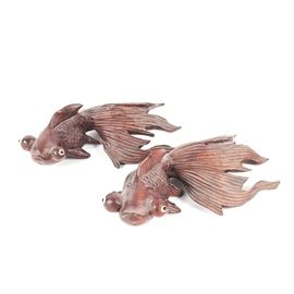 Pair of Carved Rosewood Koi Fish: A pair of carved wooden koi fish. These pieces feature a textured scale pattern to the bodies, as well as ribs to all the fins and a rosewood finish. Each fish has white and black glass eyes set in the large round eye sockets. The sculptures are unmarked.