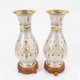 "Pair of Chinese Cloisonné Vases: A pair of matching Chinese cloisonné vases. The enameled design features lavender, blue, red and yellow floral and leaf designs on a white field. The undersides are enameled blue. Both vases have pierced wood pedestals. There is a red sticker on the underside of one vase with a gold butterfly marked ""Beijing, China"" (中國北京)."