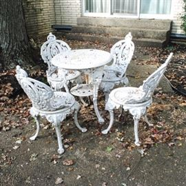 Antique Cast Iron Patio Table and Chairs: An antique Victorian white-painted cast iron patio table and chairs. This includes one round table with an ornate scrolling and pierced top and beaded edges. It rises on four sabre legs, each of which features a prominent mask at the knee, with beading leading to pad feet; a single round shelf sits between them. Each of the four chairs features a scrolling and pierced balloon back over a circular seat. They rise on sabre legs which terminate in pad feet.