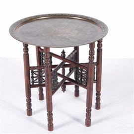 Classical Style Tray Table: A Classical style tray table. This wood table features a circular metal tray top, three intersecting stretchers with carved baluster designs, pointed finials, and six baluster legs with circular feet. The tray features a central floral medallion with diamond and zigzag borders with Greek style figural depictions. The legs fold together for compact storage. There are no visible maker's marks to the pieces.