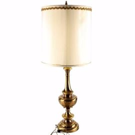 Brass Torchiere Table Lamp with Shade: A brass torchiere table lamp with shade. The lamp has a bowl-shaped glass lampshade on a turned brass body with panel accents. Other features of the light include an etched pedestal and a round base with a switch and a drum style, white lampshade with brown cloth piping and a turned brass finial.