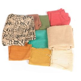 Assorted Hemp Fabric: An assortment of hemp fabric. This assortment includes colorful solid hemp fabric in pink, green, sky blue, mustard yellow, burnt orange, and more. There is also a beige piece with a overlaying number and letter pattern in black.