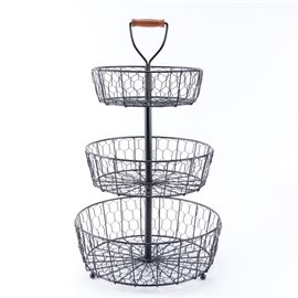 Tiered Wire Display Basket with Handle: A tiered wire display basket with handle. The basket is metal with a black finish and center pole with a metal handle that has a wood grip. Other features of the selection include three mesh style wire baskets in three sizes and the baskets stand on metal bun feet.