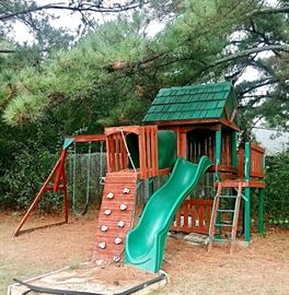 OFF-SITE ITEM Backyard playset with playhouse, wave slide, rock climbing wall, crawl through tube, and swings.