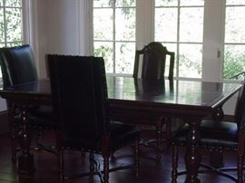 Farm table with turned legs.  Three leather chairs, also Marge Carson.  One wood chair with upholstered seat.