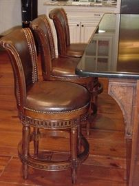 Three leather and wood bar stools with swivel seat