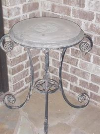 Two stone top wrought iron tables