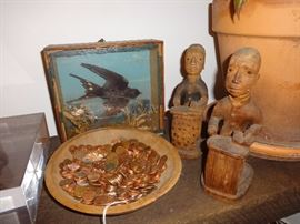 Carved colonial administrators by Thomas Ona Odulate; swallow diorama; and bowl of pennies.