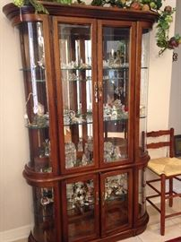 Curio cabinet loaded with collectibles including Austrian Swarovski crystal figures