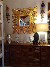 "Nice gilt wood, beveled glass wall mirror, on the buffet that matches the Drexel Esperanto suite. There's a stone Buddha head, a pair of Rosenthal-Netter foo dogs, Waterford crystal aperitif glasses and a very heavy, solid marble Surya ""Kerrigan"" lamp, that retails for over $400.00 - yep, just ask the Google."