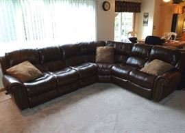 Six-section, faux leather, sectional sofa by Walter E. Smithe.  Two sections are recliners; one at each end.  Sections can rearranged to switch the long and shorter sides.
