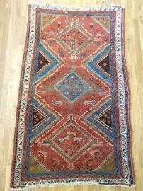 Vintage Persian tribal rug, 100% wool, hand woven, measures 5' x 7'.