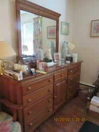 Maple chest with mirror has nine drawers and a cabinet.