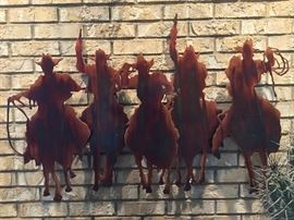 Metal cowboys on horses wall art