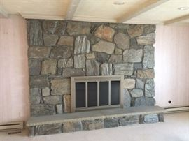 The hearth is a solid slab, new fireplace screen in silver. Painted beams and baseboard heater.