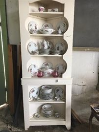 Here is corner cabinet with porcelain set