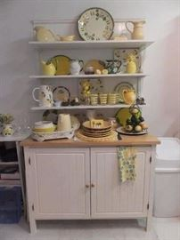 Cottage cupboard with decor.  Upper portion (shelves) are not part of the cupboard.  They are attached to the wall