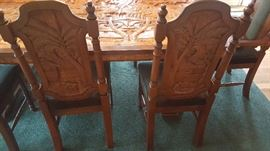 Hand carved dining room chairs with matching scenes from the table top.