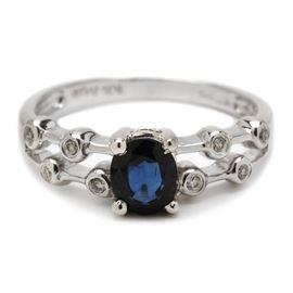 14K White Gold Natural Blue Sapphire Diamond Ring: A 14K white gold ring showcasing a prong-set natural blue sapphire to the center of split shoulders with bezel-set diamonds adorning them.