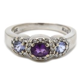 14K White Gold Amethyst, Tanzanite, and Diamond Fashion Ring: A 14K white gold fashion ring featuring an amethyst center stone with surrounded diamonds and two flanking tanzanite stones also with diamond halos.