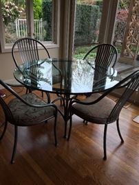 "Glass top dining table and four chairs - suitable for a covered outdoor area or indoor use  asking $380 48""round x 30""h"
