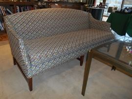 """Living Room:  A vintage curved back and arms geometric print sofa measures 72"""" long.  The tan rug with brown border measures 12' x 12.'"""