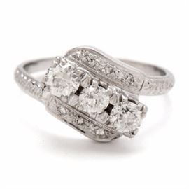 14K White Gold Vintage Ring Featuring Three Old European Cut Diamonds: A 14K white gold vintage ring featuring three old European cut diamonds prong set diagonally in a raised setting with six accent diamonds.
