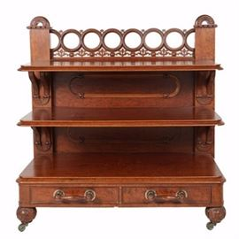Antique Victorian Three-Tier Walnut Server: An antique Victorian three-tier walnut server, circa third quarter of the 19th century. The frame features a rear gallery with a row of openwork rings supported by pierced foliate motifs alternating with cabochons. Flanking the gallery is a pair of square posts topped by arches with shallow-carved leaves and berries against a stippled ground. Directly below are three rectangular shelves with figured veneers, molded edges, and rounded corners supported by leaf- and berry-carved brackets. The two lower, back panels are applied with racetrack moldings and the base is fitted with two aligned, dovetailed drawers. The fronts have spindled handles with ball terminals and the server rises on ball-carved, front feet ending in brass casters.