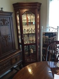 Lighted curio (display) cabinet.  Glass and wood.  Glass shelves are etched for item placement. Item beside curio is heavy wrought iron standing mirror for bedroom or bath use.   Table in front.