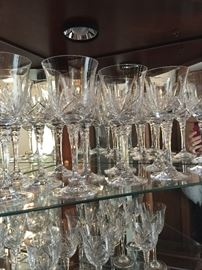 Large number of beautiful cut crystal stemware.  These are the larger water goblets.  Smaller wine glasses complete the set (shown on shelf below).  See other pictures.