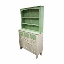 Country Style Painted Cabinet: A vintage country style painted china cabinet. The set back rectangular top features an arched opening to the two shelves backed with vertically hung beadboard. The top section is painted mint green and rests atop the sideboard. The sideboard is fitted with three aligned drawers with wood knobs over three cabinet doors. The doors open to shelved storage and the piece rises on square, tapered legs. The top, drawer fronts and knobs are painted mint green and the rest is painted white. The distressing is intentional and from use.