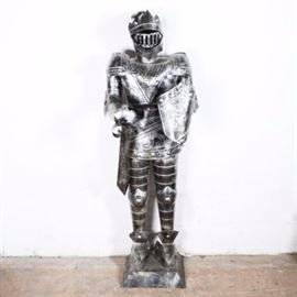 Reproduction Medieval Suit of Armor: A life-sized reproduction suit of medieval armor. This suit is made from stamped, bent and welded sheet metal. The statue is hollow and unmarked.